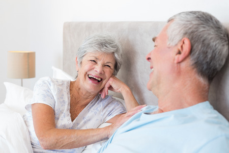 Happy senior woman looking at husband while lying in bed photo