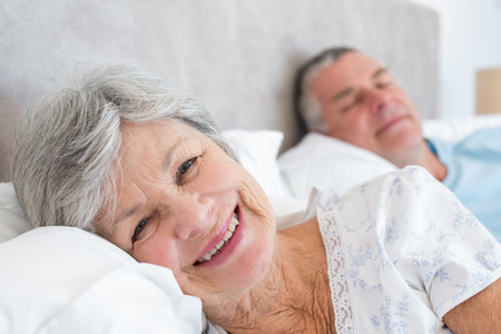 Portrait of happy senior woman lying on bed with man at home photo