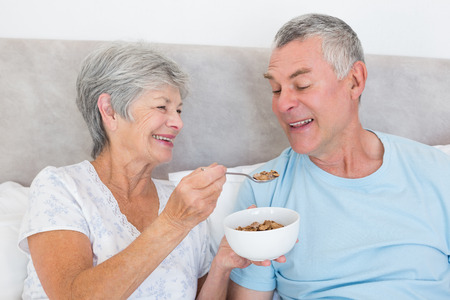 Happy senior woman feeding cereals to husband at home photo