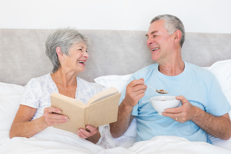 Happy senior man having cereals while wife holding book in bed at home photo
