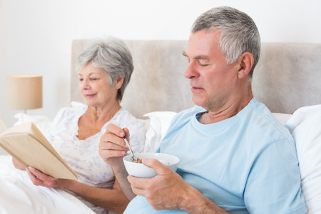 Senior man eating cereals while wife reading book in bed at home photo