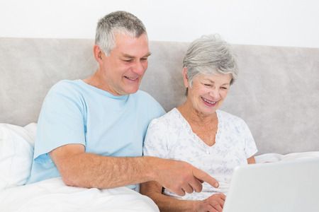 Happy senior couple using laptop together in bed at home photo