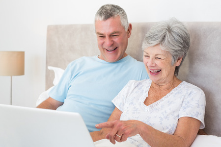 Senior couple laughing while using laptop in bed at home photo