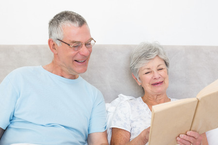 Smiling senior couple reading book in bed at home photo