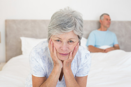 Portrait of sad senior woman with husband in bed at home photo