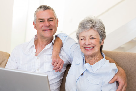 Portrait of senior couple with laptop sitting on sofa at home photo
