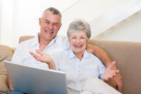 Portrait of happy senior couple with laptop on sofa photo