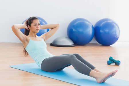 Full length of a determined young woman doing sit ups in fitness studio photo