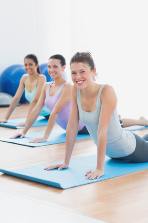 Portrait of a smiling fit class doing the cobra pose in a bright fitness studio photo