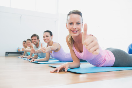 Side view portrait of fit class gesturing thumbs up at fitness studio photo