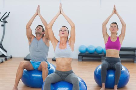 joined hands: Los j�venes deportistas con las manos juntas sentada en pelotas de ejercicio en el gimnasio