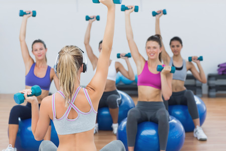 Fit class and instructor exercising with dumbbells on fitness balls in gym photo