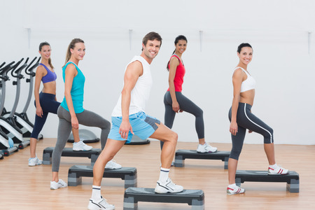 Full length of instructor with fitness class performing step aerobics exercise in gym photo