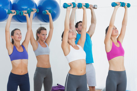 Fitness class and instructor exercising with dumbbells in the gym photo