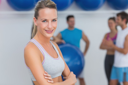 Portrait of a fit smiling young woman with friends in background at fitness studio photo