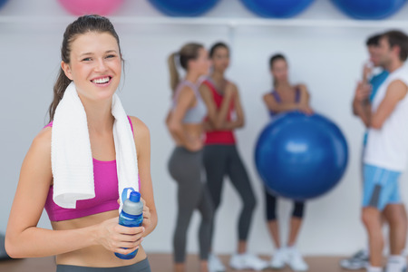 group fitness: Portrait of a fit female holding water bottle with fitness class in background at gym Stock Photo