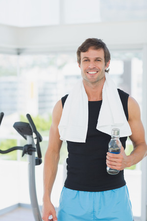 Portrait of a smiling young man holding water bottle at spinning class in a bright gym photo