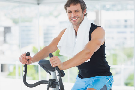 Portrait of a smiling young man working out at spinning class in a bright gym photo