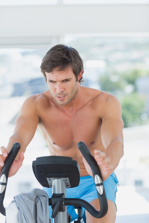 Determined young man working out at spinning class in a bright gym photo