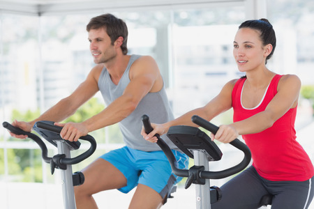 Fit young couple working out at spinning class in a bright gym photo