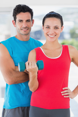 Portrait of a fit young couple standing with dumbbell in a bright exercise room photo