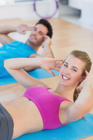 sit ups: Side view portrait of a smiling young couple doing sit ups at a gym Stock Photo