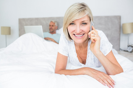 Portrait of a happy mature woman using cellphone while man using laptop in bed at home photo