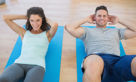 adult couple: Portrait of smiling couple doing sit ups at a gym