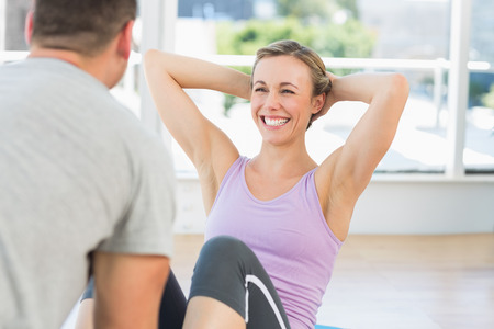 Male trainer assisting fit woman in doing sits up in exercise room Stock Photo