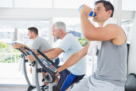 Side view of man on exercise bike drinking water at fitness studio photo