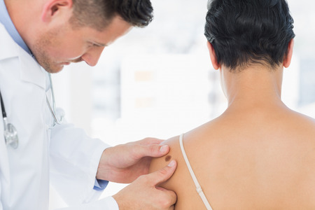 dermatologist: Male doctor examining melanoma on woman in clinic Stock Photo