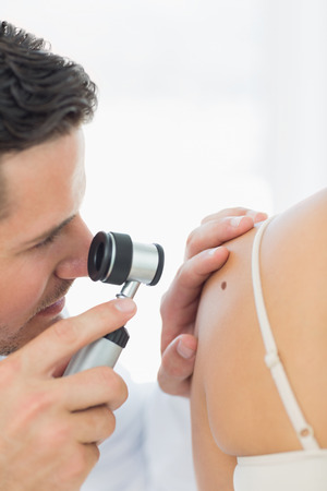 Closeup of male doctor checking mole on woman in clinic photo
