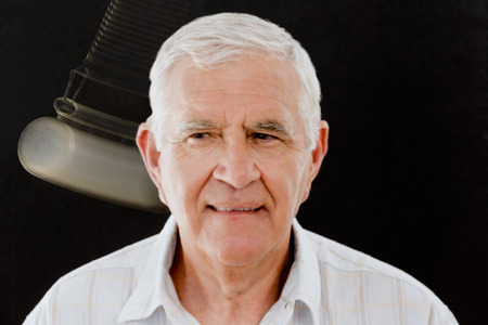 Senior man being hypnotized with pocket watch over black background