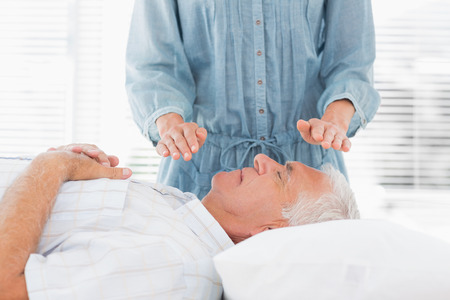 Female therapist performing Reiki over senior man at health spa Stock Photo - 27111962