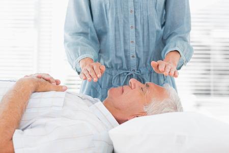 female therapist: Female therapist performing Reiki over senior man at health spa