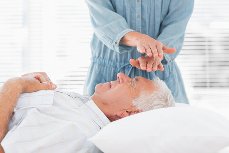 Massage therapist performing Reiki over forehead of senior man at health spa photo