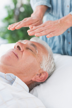 reiki: Senior man having Reiki treatment by massage therapist at spa