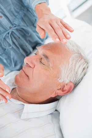 Closeup of senior man receiving Reiki treatment by therapist at health spa photo