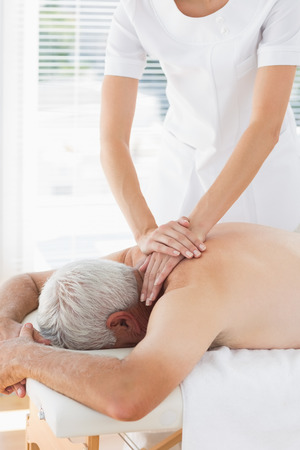 Female physiotherapist massaging back of senior patient in clinic photo