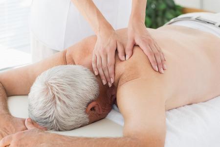 Female massage therapist massaging back of senior man in medical office photo