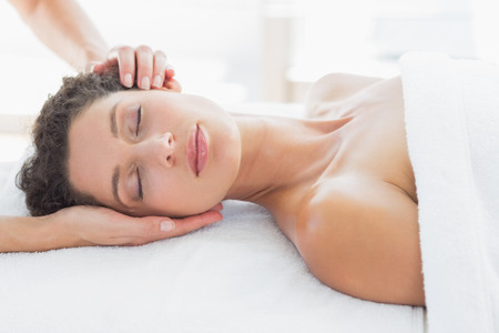 Beautiful young woman receiving head massage in health spa photo