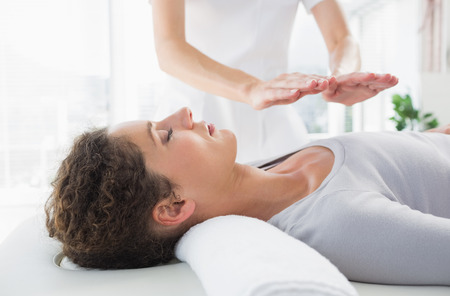 alternative therapies: Attractive young woman having reiki treatment in health spa