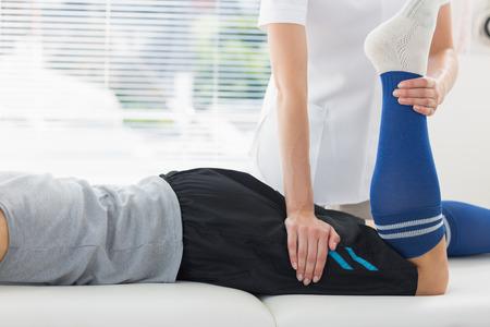 Fisioterapeuta trabajando en la pierna del hombre joven Foto de archivo