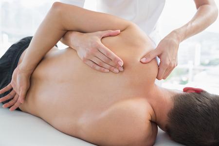 fisioterapia: Imagen recortada de fisioterapeuta masajeando hombre en el hospital Foto de archivo