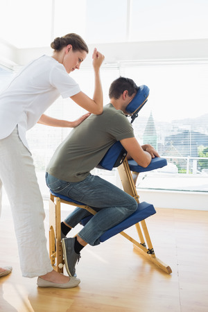 massage chair: Full length of professional female therapist giving massage to man in hospital