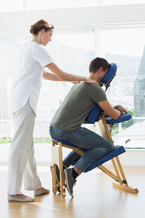 Full length of man receiving shoulder massage from therapist in hospital photo