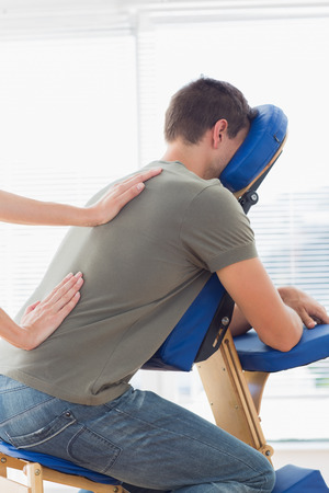 cropped image: Cropped image of therapist giving back massage to man on massage chair in hospital Stock Photo