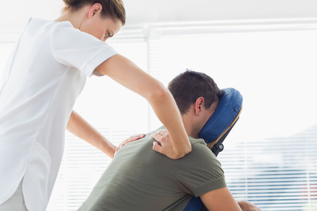 Female physiotherapist giving back massage to man in hospital photo