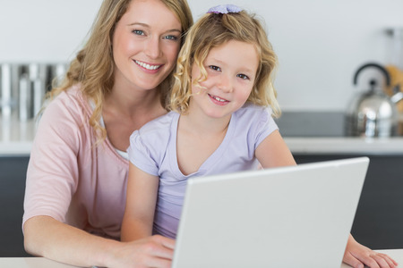 Portrait of smiling mother and daughter with laptop in kitchen photo