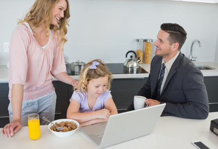 Couple looking at each other while daughter using laptop at table in house photo